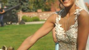 A noiva loura bonita feliz com o ramalhete encantador do sorriso e do casamento está levantando com suas damas de honra no jardim video estoque