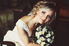 A noiva loura bonita sorri guardando um ramalhete do casamento perto de seu fá fotos de stock royalty free
