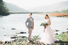Noiva loura feliz à moda elegante e noivo lindo no fundo de um rio bonito nas montanhas imagem de stock