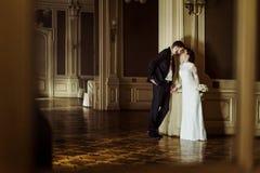Noiva luxuosa à moda e noivo elegante considerável que beijam no b foto de stock royalty free