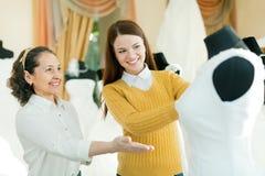 A noiva das ajudas do Saleswoman escolhe o vestido nupcial Fotografia de Stock