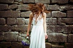 A noiva mistura seu cabelo em torno de estar atrás de uma parede de pedra Imagem de Stock