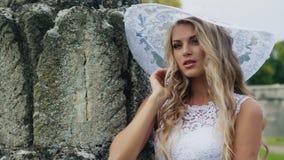 Noiva modesta em um chapéu branco que olha a câmera video estoque