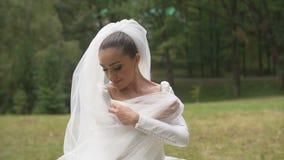 A noiva moreno atrativa bonita com sorriso bonito está envolvendo-se no véu no parque vídeos de arquivo