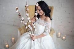 Noiva moreno bonita bronzeada no vestido de casamento branco que senta-se na cadeira Nas mãos que guardam os ramos do algodão fotografia de stock