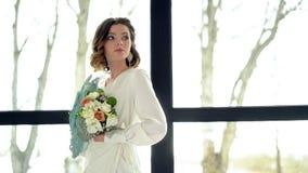 A noiva moreno bonita guarda um ramalhete da flor perto do window-2 Tiara bonita no cabelo, composição profissional vídeos de arquivo