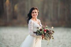 Noiva moreno lindo no vestido elegante que guarda o ramalhete que levanta perto da floresta e do lago fotografia de stock royalty free