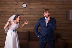 Noiva na gritaria branca do vestido e do véu no noivo fotografia de stock royalty free