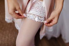A noiva no branco põe sobre uma atadura a céu aberto bonita sobre um pé elegante Conceito do casamento fotografia de stock