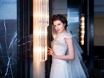 Noiva no interior azul no vestido branco longo Foto de Stock