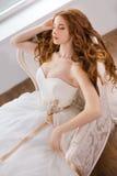 Noiva no vestido bonito que coloca o descanso no sofá dentro Fotos de Stock Royalty Free