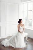 Noiva no vestido bonito que senta-se na cadeira dentro foto de stock