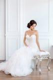 Noiva no vestido bonito que senta-se na cadeira dentro imagens de stock