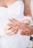 Noiva no vestido branco que põe a aliança de casamento sobre o dedo dos noivos Fotos de Stock Royalty Free