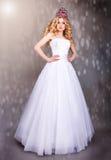 Noiva no vestido de casamento branco em um fundo cinzento Foto de Stock