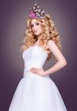 Noiva no vestido de casamento branco em um fundo cinzento Fotografia de Stock