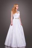 Noiva no vestido de casamento branco em um fundo cinzento Imagem de Stock