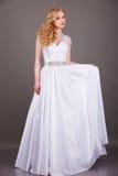 Noiva no vestido de casamento branco em um fundo cinzento Foto de Stock Royalty Free