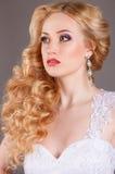 Noiva no vestido de casamento branco em um fundo cinzento Imagens de Stock