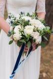A noiva no vestido de casamento branco guarda um ramalhete do casamento foto de stock