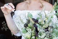 A noiva no vestido de casamento branco mantém um ramalhete do casamento com papoilas exterior fotos de stock royalty free