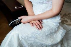 A noiva no vestido de casamento branco senta e mantém um espelho disponivel imagem de stock