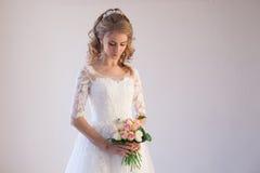 Noiva no vestido de casamento com um ramalhete das flores Imagens de Stock Royalty Free