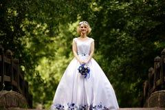 Noiva no vestido de casamento da beleza que está na ponte Foto de Stock