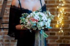 A noiva no vestido de molho preto que está em um fundo do sótão com festões e posses um ramalhete do casamento foto de stock royalty free