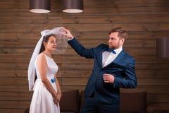 Noiva no vestido e véu contra o noivo no terno imagem de stock royalty free