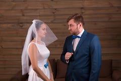 Noiva no vestido e véu contra o noivo no terno fotografia de stock royalty free