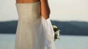 A noiva no vestido nupcial perfeito está no beliche perto da água video estoque