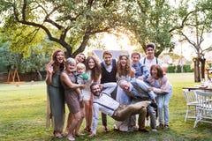 Noiva, noivo e convidados levantando para a foto no copo de água fora no quintal imagem de stock royalty free