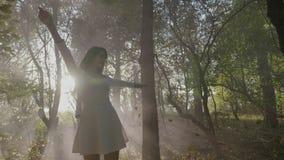 Noiva nova bonita com o vestido branco simples que tem o divertimento no parque entre as folhas de outono de queda e no fumo no m filme