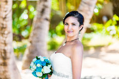 Noiva nova bonita em um vestido de casamento branco com o ramalhete em h Fotos de Stock Royalty Free