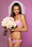 A noiva nova bonita no véu branco e empalidece - a roupa interior cor-de-rosa do laço com o ramalhete das peônias à disposição Foto de Stock