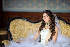 A noiva nova bonita senta-se em um sofá magnífico em um interior antigo imagem de stock royalty free