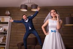 Noiva nova com telefone celular e o noivo brincalhão fotos de stock