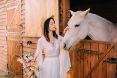 A noiva nova do estilo do boho está afagando o cavalo branco foto de stock royalty free