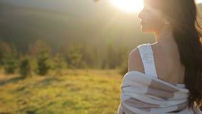 Noiva nova e bonita com tampa na inclinação da montanha no por do sol Tempo ventoso Cabelo e véu que agitam no filme