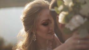 A noiva nova feliz olha seu noivo Pares novos do amor que sorriem e que beijam no banco de rio vídeos de arquivo