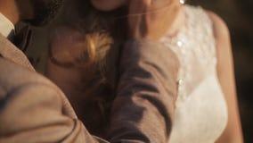 A noiva nova feliz olha seu noivo Pares novos do amor que sorriem e que beijam no banco de rio video estoque