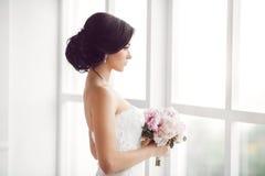 Noiva nova impressionante que guarda o ramalhete foto de stock