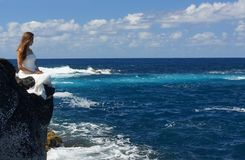 Noiva nova no vestido de casamento branco que senta-se na costa da rocha e que olha o oceano na ilha de Miguel do Sao, Açores Fotografia de Stock Royalty Free