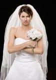 Noiva nova olhando de sobrancelhas franzidas no vestido e no véu de casamento Foto de Stock