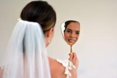 A noiva olha si mesma no espelho em seu dia do casamento Imagem de Stock Royalty Free