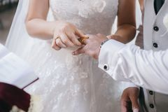 A noiva põe a aliança de casamento sobre o dedo do ` s do noivo fotos de stock