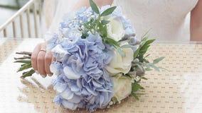 A noiva põe as flores do casamento sobre a tabela video estoque