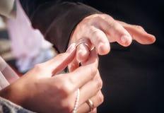 A noiva põe sobre um anel uma mão ao noivo Imagem de Stock
