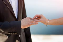 A noiva põe um anel sobre a mão do noivo fotografia de stock